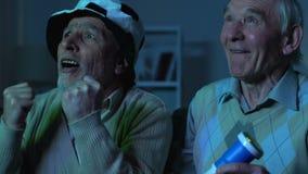 Fanáticos del fútbol envejecidos que miran el partido de la TV el animar para el equipo preferido, entretenimiento almacen de metraje de vídeo