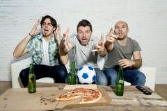 Fanáticos del fútbol fanáticos de los amigos que ven la TV hacer juego con la tensión del sufrimiento de las botellas y de la piz Imagen de archivo libre de regalías