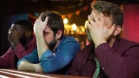 Fanáticos del fútbol multiétnicos que hacen el facepalm, decepcionado con pérdida del juego, barra metrajes