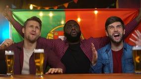 Fanáticos del fútbol multirraciales ansiosos con el partido perdidoso del equipo infeliz portugués de la bandera almacen de video