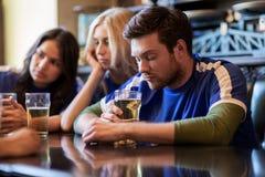 Fanáticos del fútbol o amigos con la cerveza en la barra de deporte Imagenes de archivo