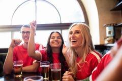Fanáticos del fútbol o amigos con la cerveza en la barra de deporte Fotografía de archivo libre de regalías