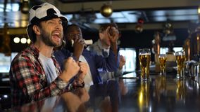 Fanáticos del fútbol que miran campeonato en el pub, extremadamente feliz sobre meta que gana almacen de video