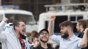 Fanáticos del fútbol que miran la cámara que salta y que sonríe en cierre de la cámara lenta para arriba metrajes