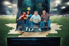 Fanáticos del fútbol del fútbol que se sientan en el sofá y la TV de observación en el medio de un campo de fútbol Imagen de archivo libre de regalías