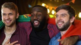 Fan?ticos del f?tbol sonrientes con la bandera portuguesa que cantan himno nacional antes de partido almacen de metraje de vídeo