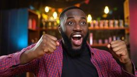 Fan afroamericano extremadamente feliz que celebra la victoria preferida del equipo en pub almacen de video
