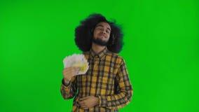Fan afroamericano soddisfatto della tenuta dell'uomo delle banconote dei soldi in sue mani e di esame della macchina fotografica  archivi video