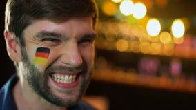 Fan alemán alegre con la bandera en mejilla que grita y que celebra la victoria, meta metrajes