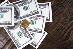 Fan av hundra dollarräkningar och en dollar mynt på en träbakgrund Royaltyfri Fotografi