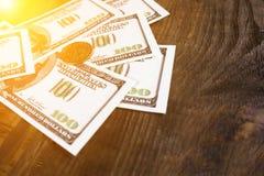 Fan av hundra dollarräkningar och en dollar mynt på en träbakgrund Arkivfoton