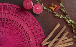 Fan, bougies, cannelle, et herbes rouges de hande sur le fond en bois Images stock