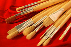 Fan of brushes. With wooden handle, on a red fabric stock images