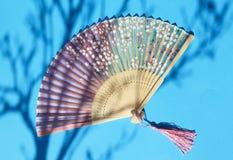 Fan chinoise de main sur le fond bleu avec l'ombre de l'arbre de fleur photographie stock libre de droits