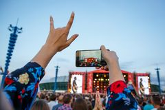 Fan in the crowd using smart phone and taking a picture of favorite musician band at music festival. Royalty Free Stock Images