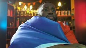 Fan d'afro-américain avec le match de observation de drapeau français dans le bar, renversement au sujet de défaite banque de vidéos