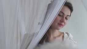 Fan d'ondeggiamento della piuma bianca della donna sveglia del ritratto su fondo bianco Serie reale della gente Nascondendosi die video d archivio