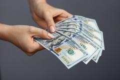 Fan de 100 billetes de banco del dólar en manos de la mujer Fotos de archivo libres de regalías