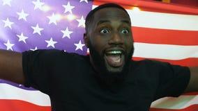 Fan de deportes afroamericana que agita la bandera de los E.E.U.U. en la barra, meta del equipo nacional que disfruta metrajes