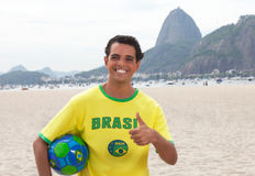Fan de deportes brasileña con la bola en Rio de Janeiro que muestra el pulgar para arriba Fotos de archivo libres de regalías