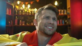 Fan de deportes cauc?sica que agita la bandera espa?ola en el pub, descontentado sobre derrota del equipo almacen de video