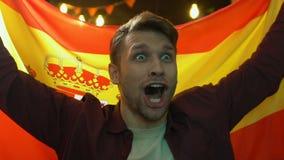 Fan de deportes emocionada que agita la bandera española en la barra, victoria del equipo nacional que disfruta metrajes