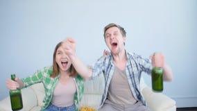 Fan de deportes emocionado de los pares que ve la TV en un sofá en la sala de estar almacen de metraje de vídeo