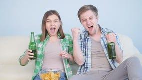 Fan de deportes emocionado de los pares que ve la TV en un sofá en la sala de estar metrajes