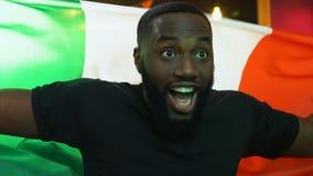 Fan de deportes negra alegre que agita la bandera italiana en la barra que disfruta la victoria preferida del equipo metrajes