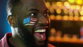 Fan de deportes negro con la bandera americana en mejilla que disfruta la victoria preferida del equipo almacen de video