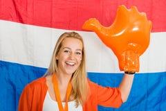 Fan de deportes que lleva una mano anaranjada inflable que anima en o delantero Fotografía de archivo libre de regalías