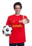 Fan de foot espagnol avec les cheveux noirs et boule montrant le pouce  Images libres de droits