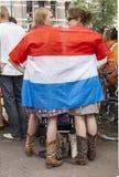 Fan de foot néerlandais fou dans l'orange et enveloppé dans le drapeau national photographie stock