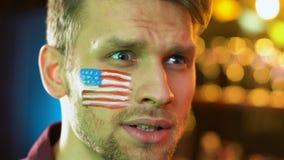 Fan de football am?ricain heureuse au sujet de la victoire pr?f?r?e d'?quipe, drapeau peint sur la joue banque de vidéos