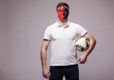 Fan de futebol albanês com a bola no jogo da equipa nacional de Albânia no fundo cinzento Fotografia de Stock