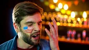 Fan de futebol ansioso com a bandeira americana no mordente desagradado com resultado do jogo imagens de stock royalty free