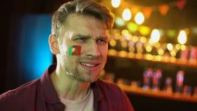 Fan de futebol ansioso com a bandeira portuguesa no mordente desagradado com resultado do fósforo video estoque