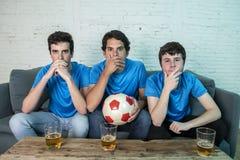 Fan de futebol desapontados que olham um fósforo de futebol imagens de stock