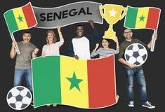 Fan de futebol diversos que guardam a bandeira de Senegal fotografia de stock