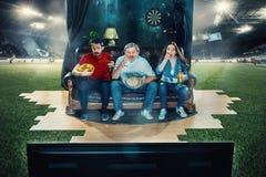 Fan de futebol do futebol que sentam-se no sofá e na tevê de observação no meio de um campo de futebol Fotos de Stock