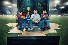 Fan de futebol do futebol que sentam-se no sofá e na tevê de observação no meio de um campo de futebol Imagem de Stock Royalty Free