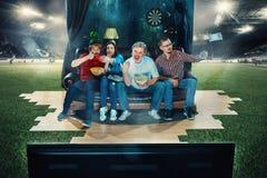 Fan de futebol do futebol que sentam-se no sofá e na tevê de observação no meio de um campo de futebol Foto de Stock