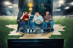 Fan de futebol do futebol que sentam-se no sofá e na tevê de observação no meio de um campo de futebol Fotografia de Stock