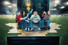 Fan de futebol do futebol que sentam-se no sofá e na tevê de observação no meio de um campo de futebol Imagens de Stock Royalty Free