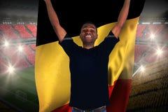 Fan de futebol entusiasmado no preto que cheering guardando a bandeira de Bélgica Foto de Stock