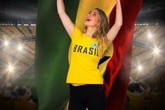 Fan de futebol entusiasmado no tshirt de Brasil que guarda a bandeira de ghana Foto de Stock