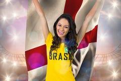 Fan de futebol entusiasmado no tshirt de Brasil que guarda a bandeira de Inglaterra Imagens de Stock
