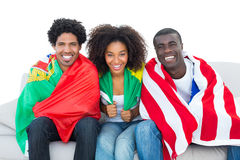 Fan de futebol felizes envolvidos nas bandeiras que sorriem na câmera Fotos de Stock Royalty Free