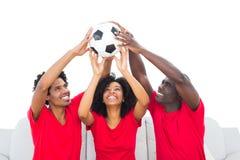 Fan de futebol felizes na bola vermelha da sustentação fotos de stock royalty free