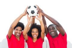 Fan de futebol felizes na bola vermelha da sustentação fotografia de stock royalty free